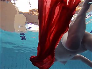 red clad teen swimming with her eyes opened